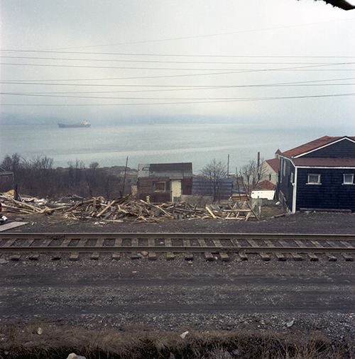 Colour photo of house with a demolished structure beside it.
