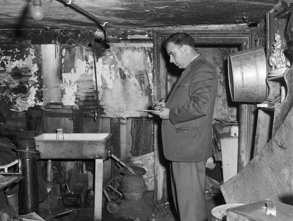 Black and white image of inspector writing in notepad in basement surrounded by debris.