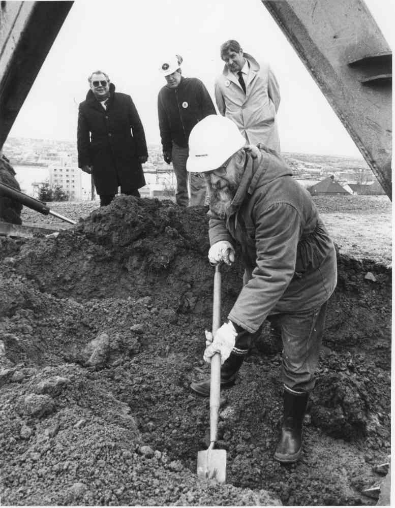 Black and white photo of Lou Collins digging with a shovel beneath an excavator, with City officials looking on.