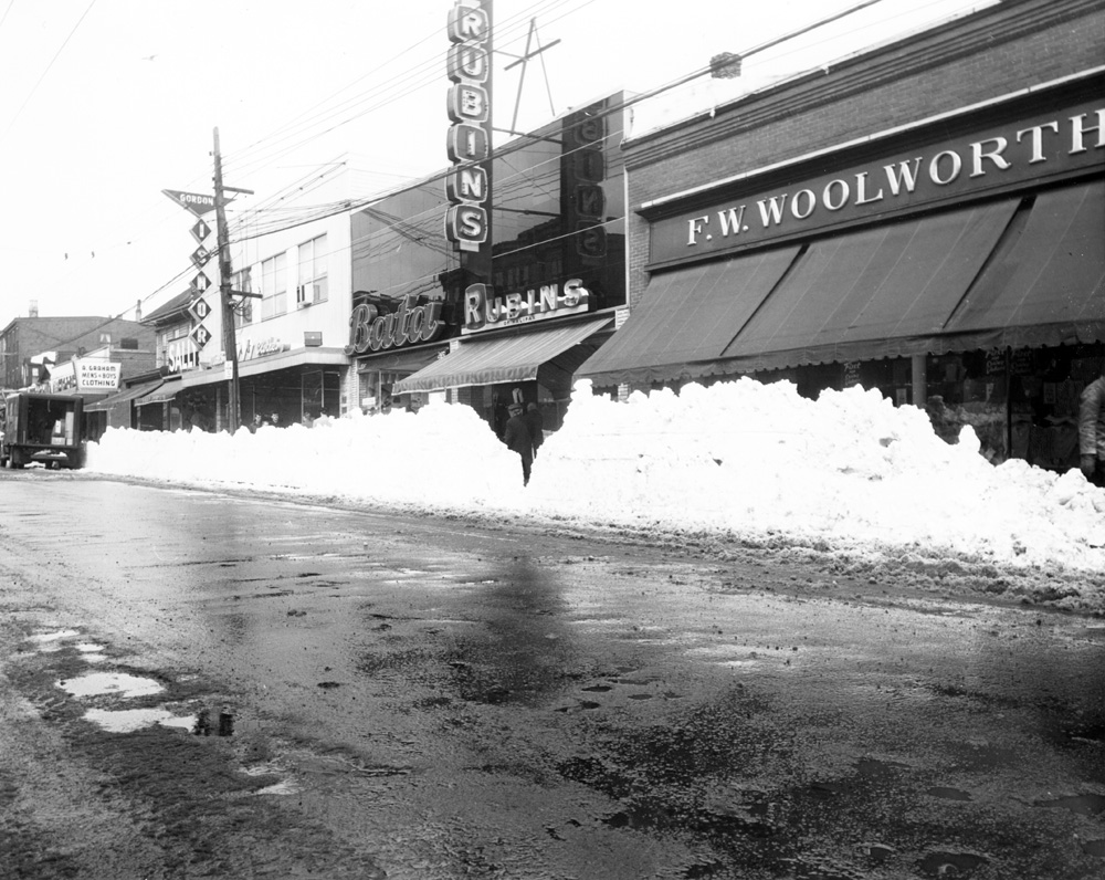 Black and white photo showing shops on Gottingen St. in winter