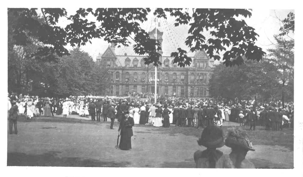 Black and white photo of group gathering in Grand Parade with City Hall in background.