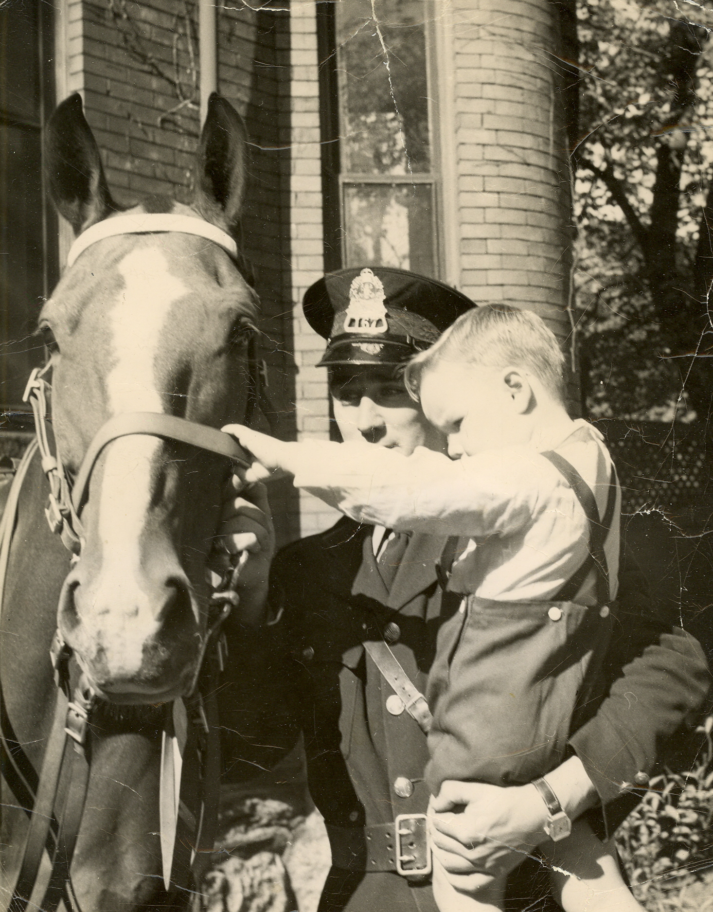 Black-and-white photo of Constable Art Francis holds a boy from the Halifax Infants Home, petting a horse