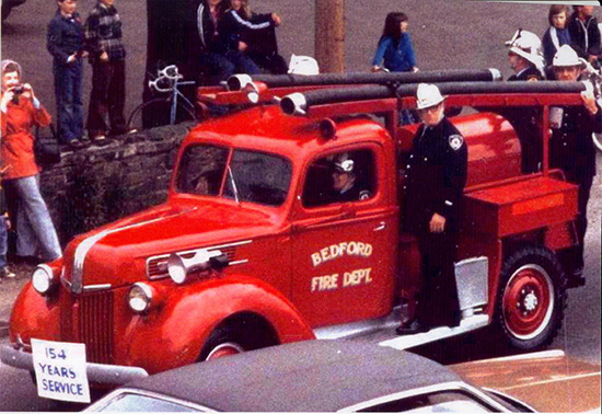 Colour photo of firefighters riding vehicle