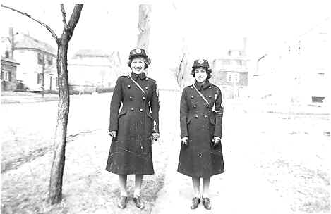 Black & white photo of Keshen sisters standing in uniform in front of houses.