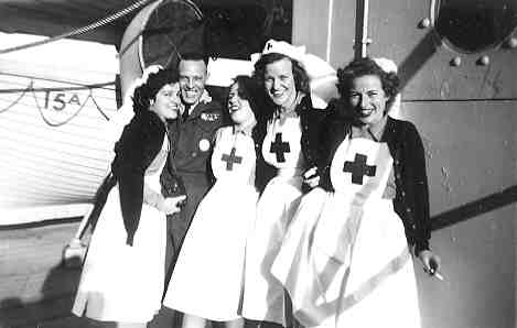 Black & white photo of 4 young women in Red Cross uniforms and 1 male soldier on the deck of a ship..