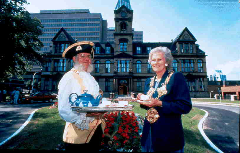 Colour photo standing outside City Hall holding a tray of tea.