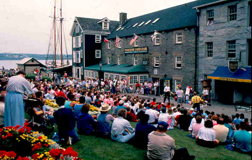 Colour photo of buskers entertaining crowds with schooner in background.