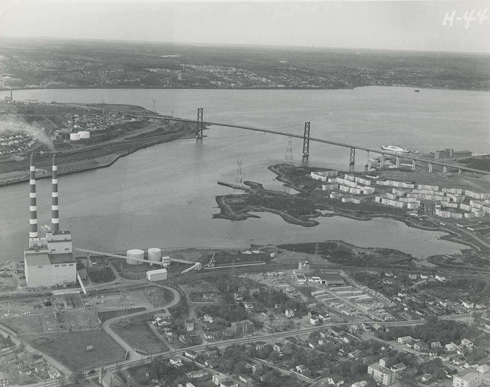 Black and white oblique aerial photograph looking northwest from Windmill Road towards the narrows and MacKay Bridge, showing 2 stacks at the Tuft's Cove generating Station, Shannon Park the Bedford Institute of Oceanography and across the Harbour to a demolished Africville and the Rockhead city prison lands.