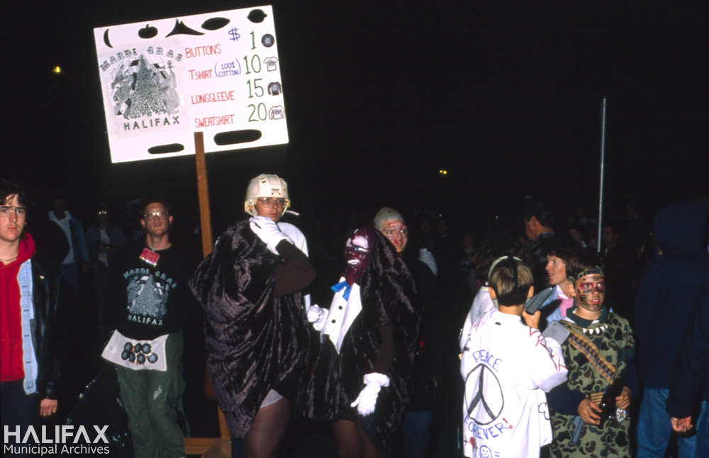 Colour photo of costumed partiers including vendor selling Mardi Gras Halifax Tshirts, buttons, etc.