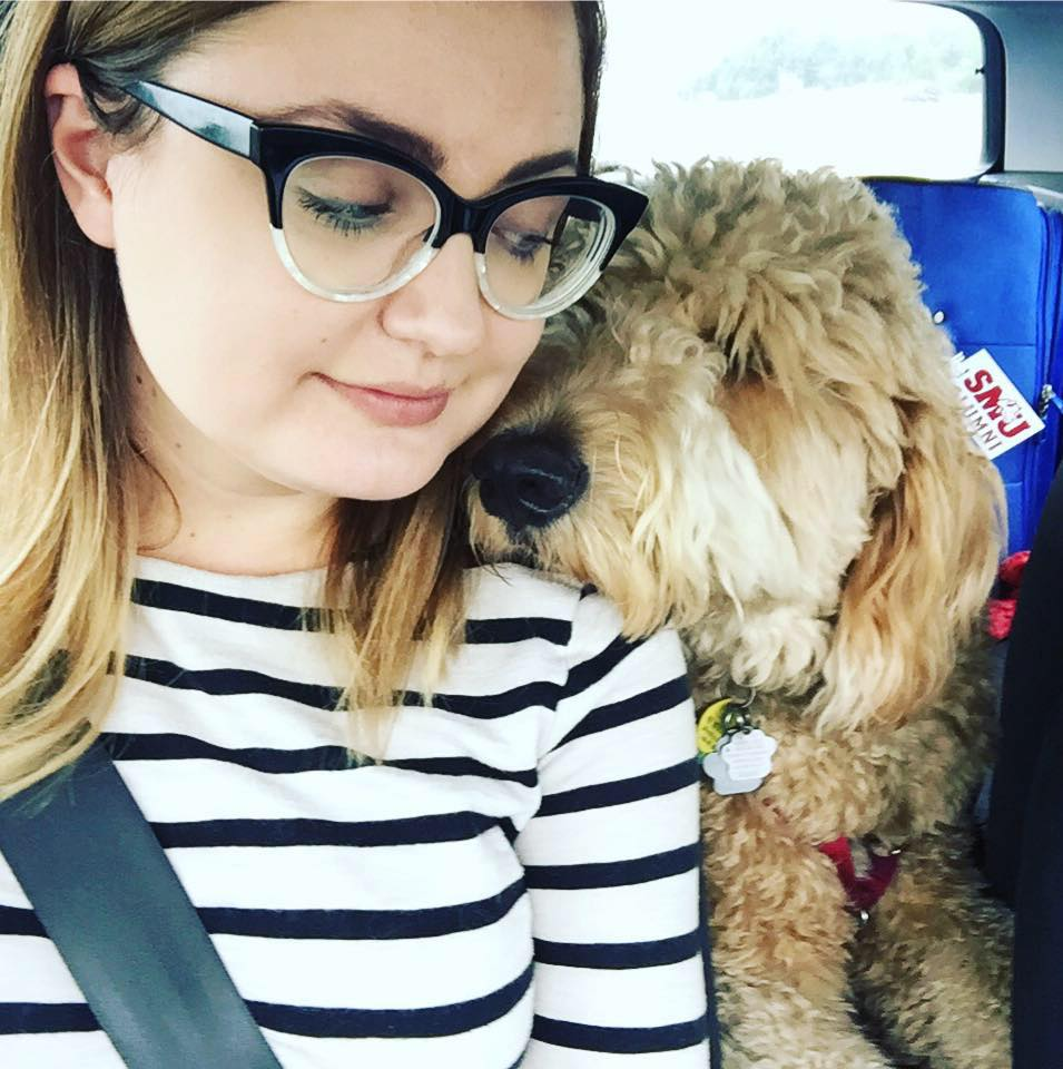 Photo of Sarah MacDonald, sitting in a car with her dog
