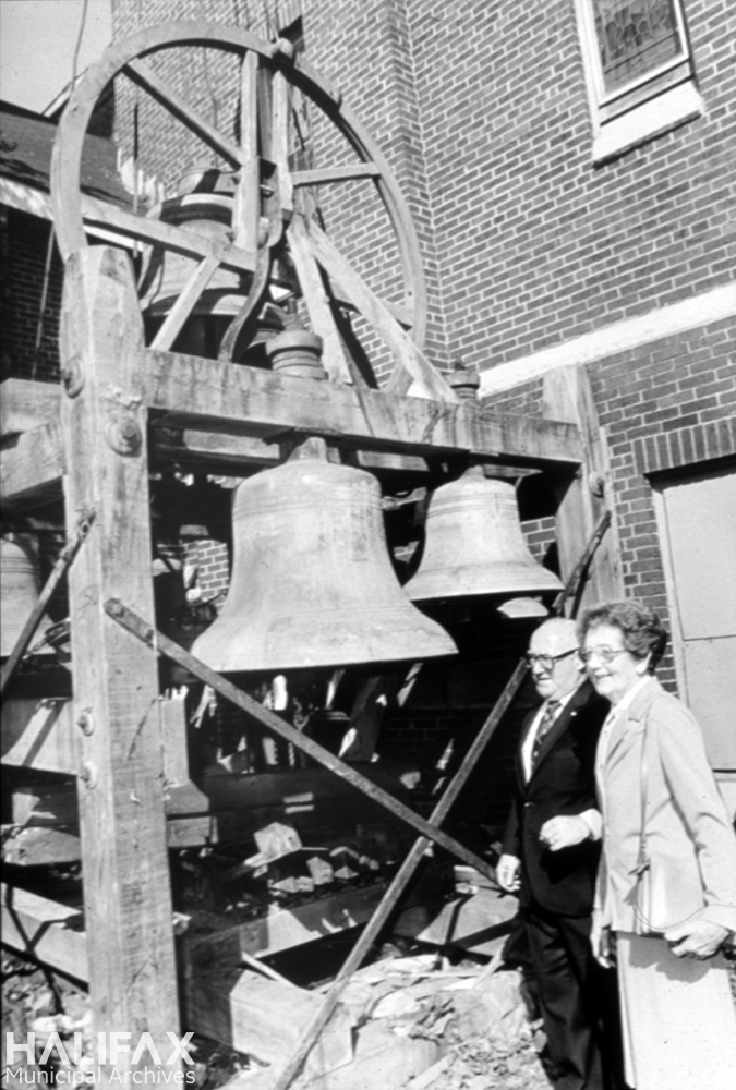 Black and white photograph of a man and woman beside church bell carillon
