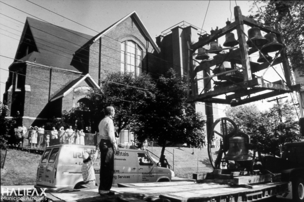 Black and white photograph of church bell carillon being loaded onto a flatbed truck