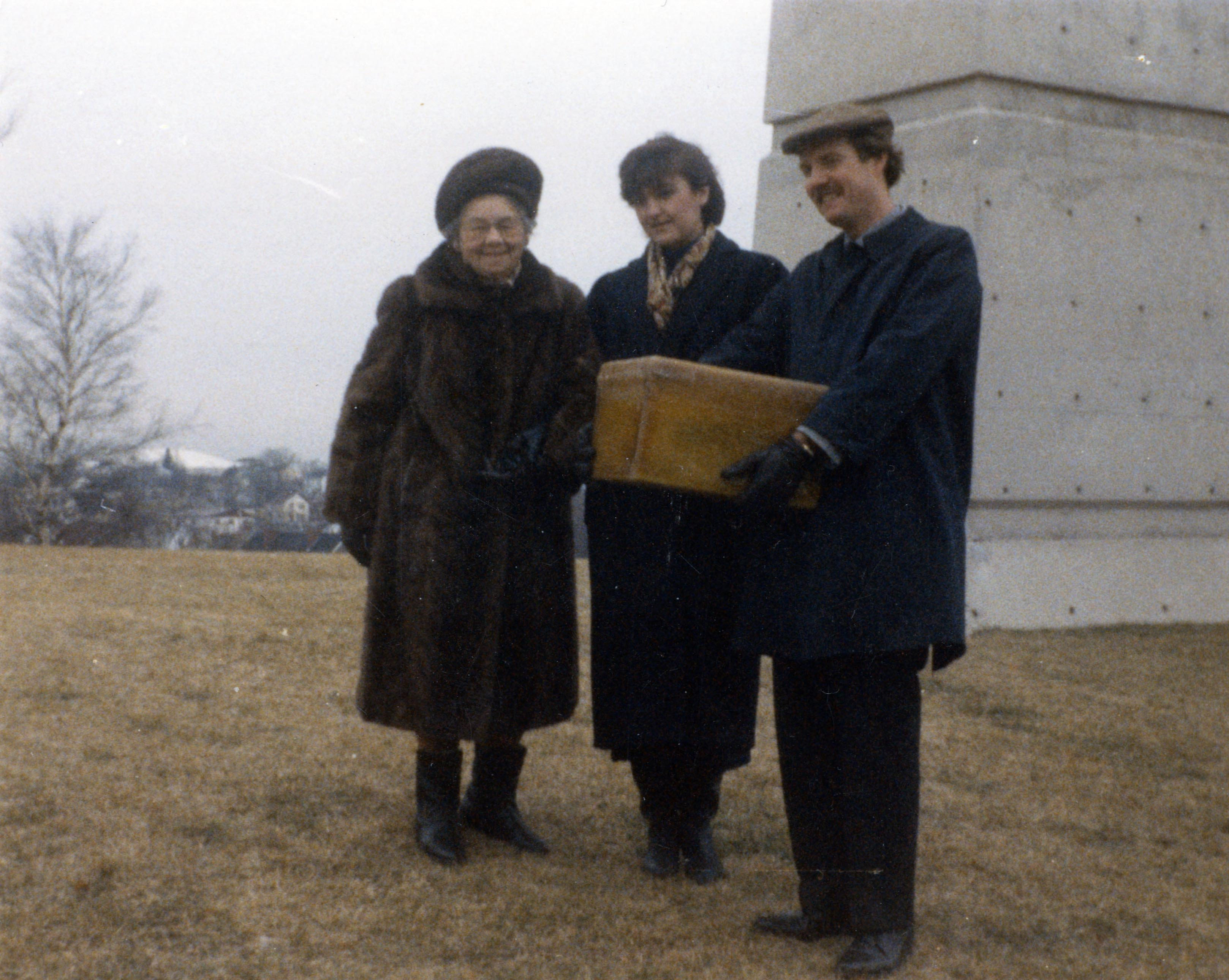 Colour photo of Explosion survivor, Millicent Upham Swindells and her grand-daughter Anne Louise Ihasz pose with Committee member Alec McLeave just before they place the time capsule, in front of the Memorial Bell Tower.