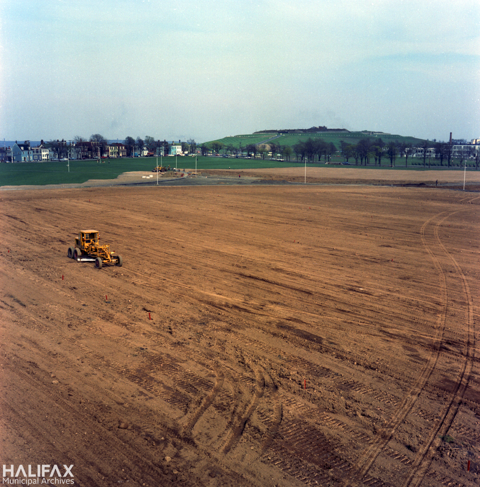 Colour photograph of a field being graded using heavy machinery