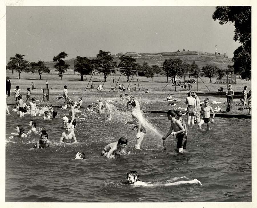 Black and white photo of children swimming with Citadel and Common in background