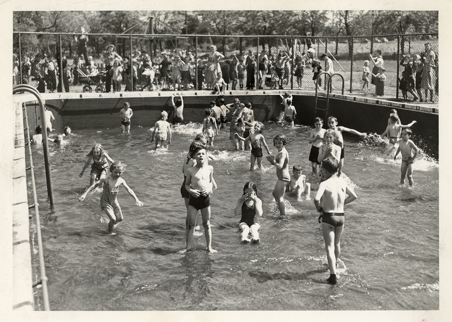 Black and white photo of locals in a swimming pool