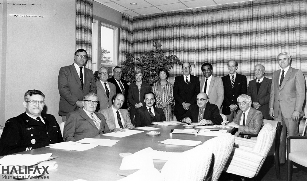 Black and white group portrait of committee in board room