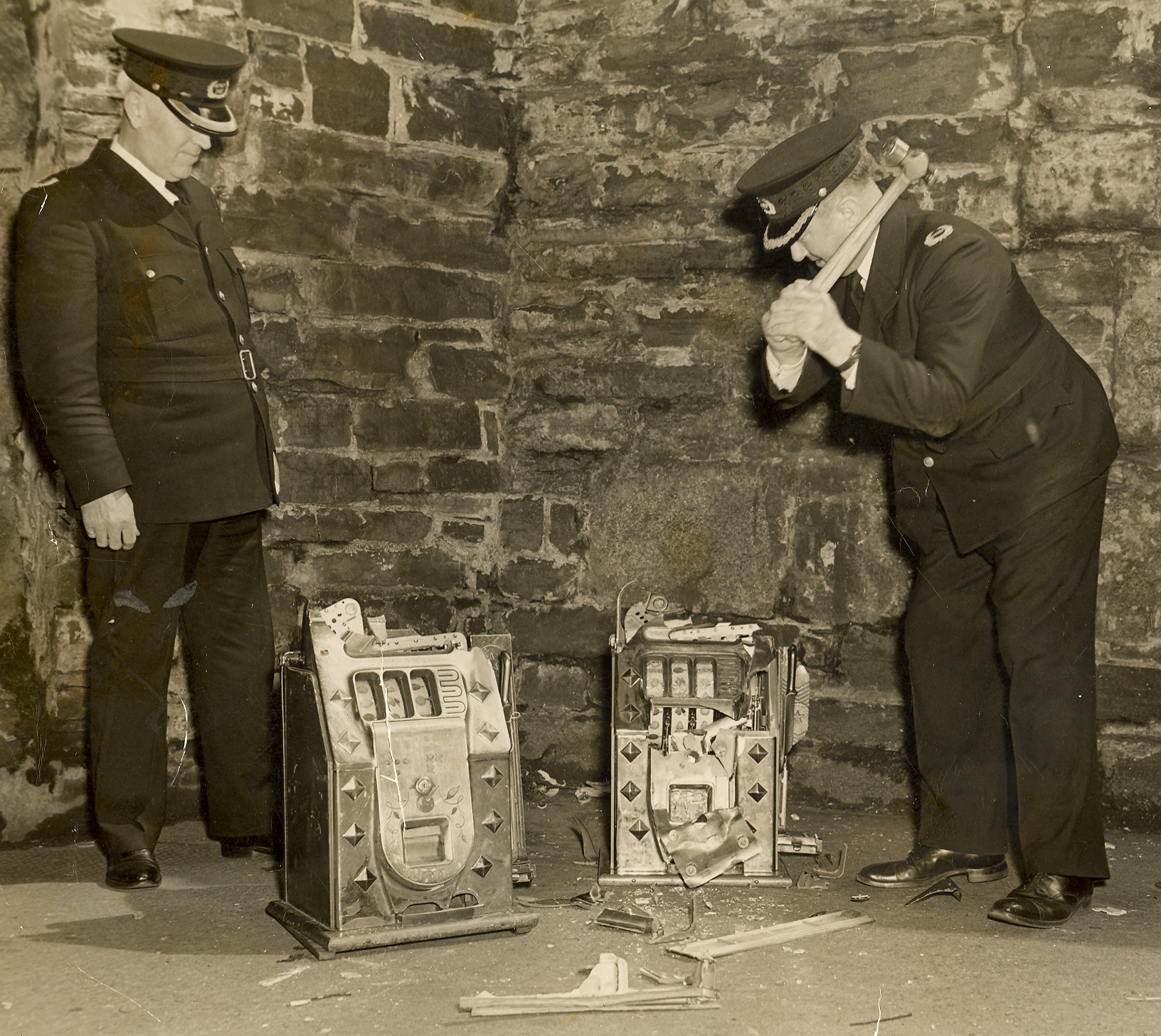 Black and white photograph of policemen smashing a slot machine with a hammer.