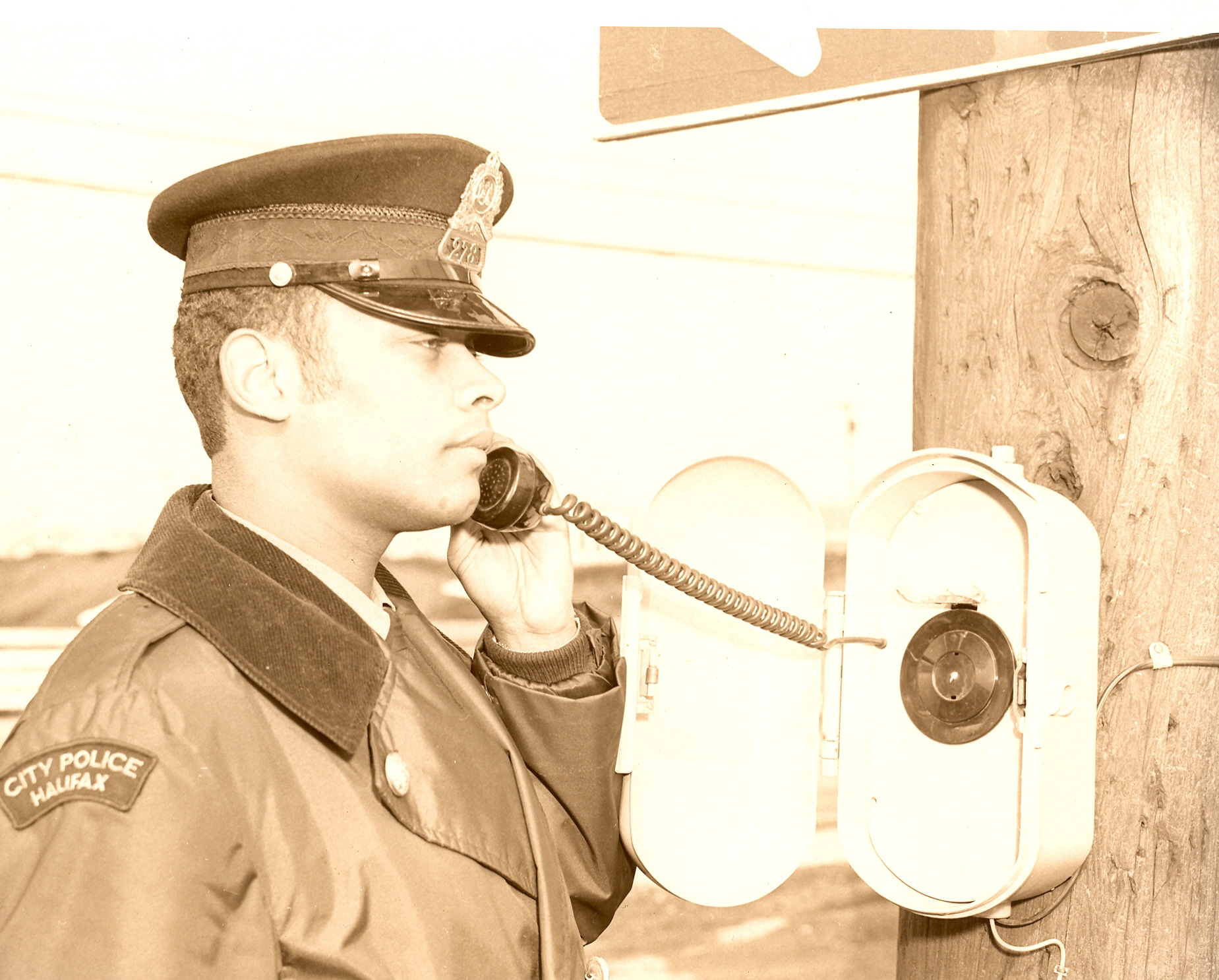 Black and white photo of African Nova Scotian officer using call-box