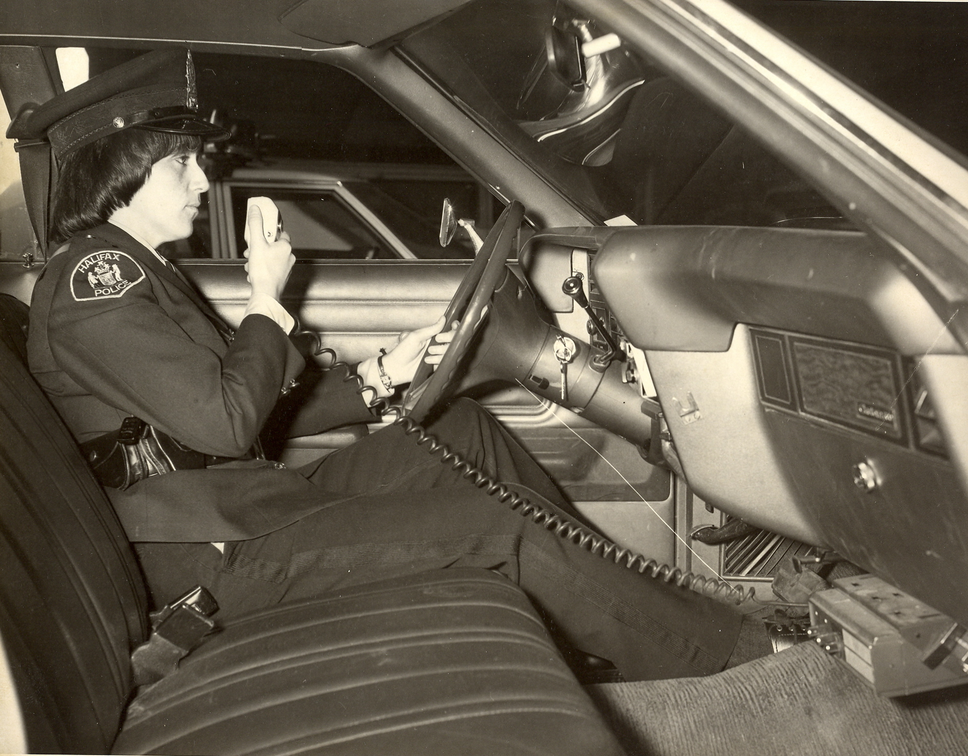 Black and white photo of female officer sitting in car talking on radio