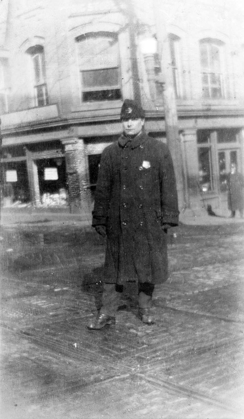 Black and white photo of officer standing in street