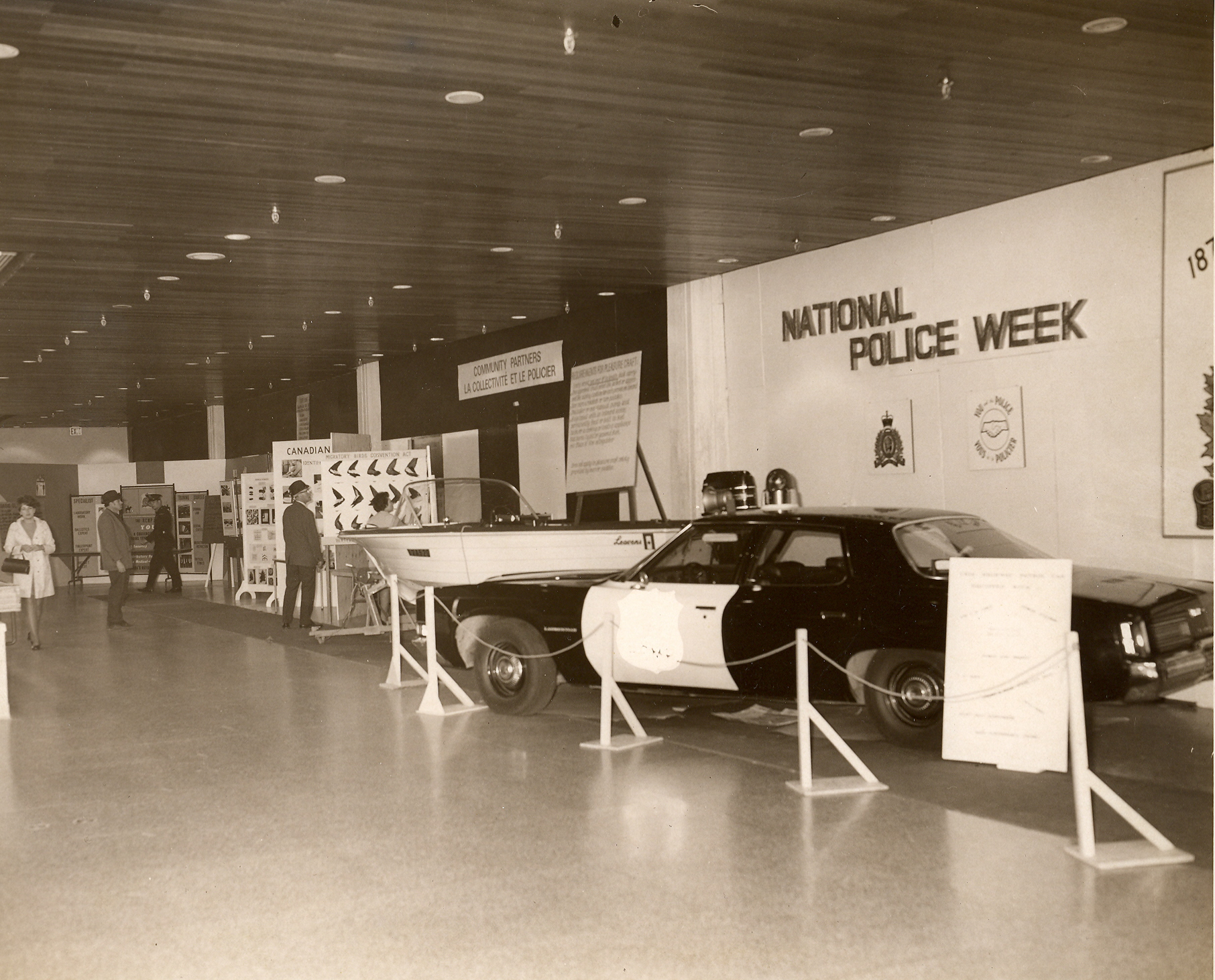 Black and white photo of a cruiser on display under a National Police Week banner