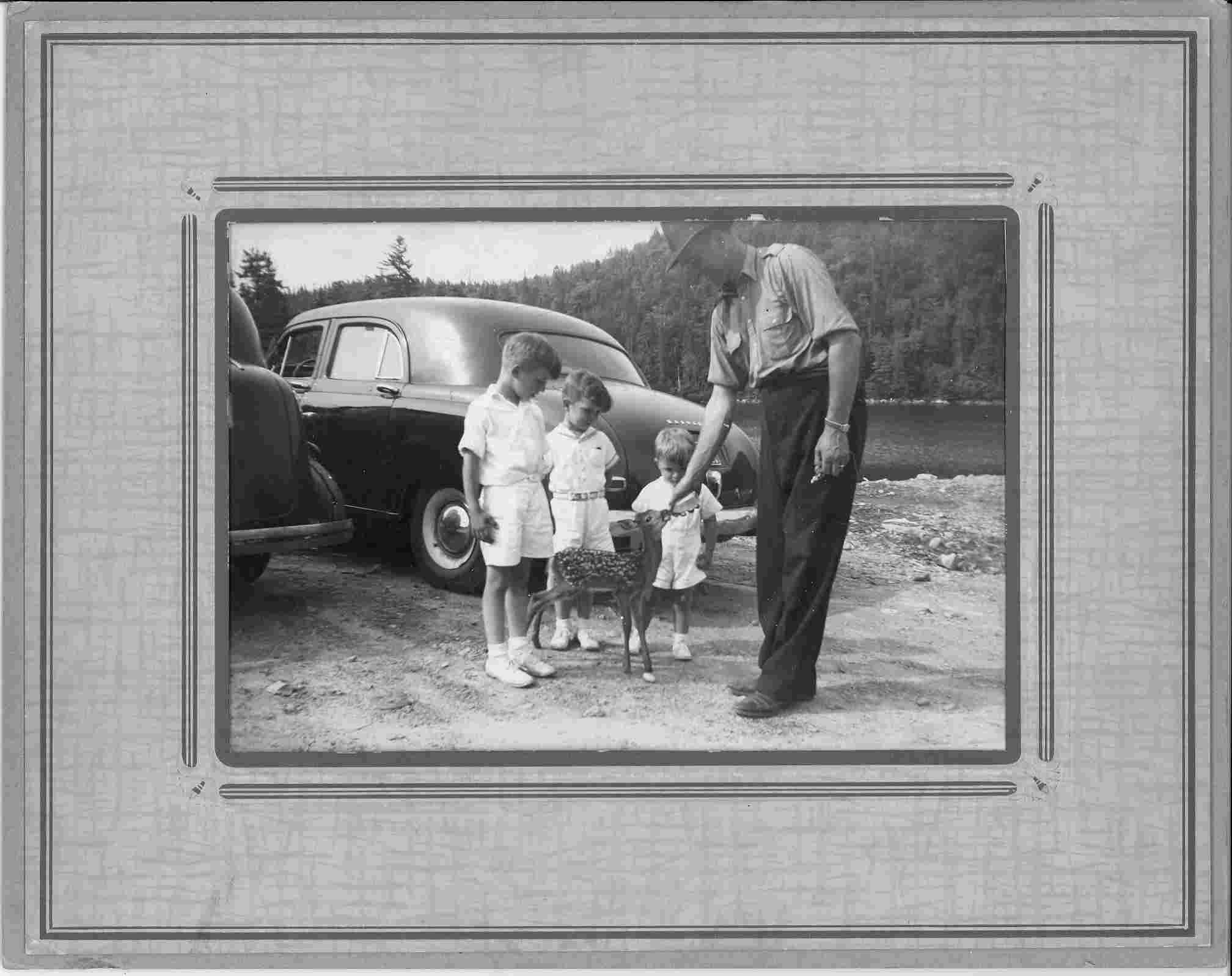 Black and white photo of a police office and three boys feeding a deer.