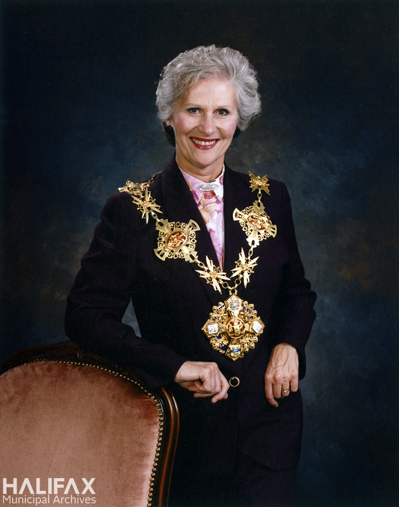 COlour photograph of a woman stadning beside a chair wearing the Mayor's chain of office for the City of Halifax