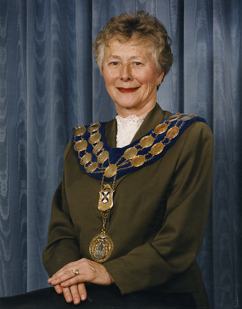 Colour photograph of a woman standing beside a chair wearing the mayor's chain of office for the City of Dartmouth