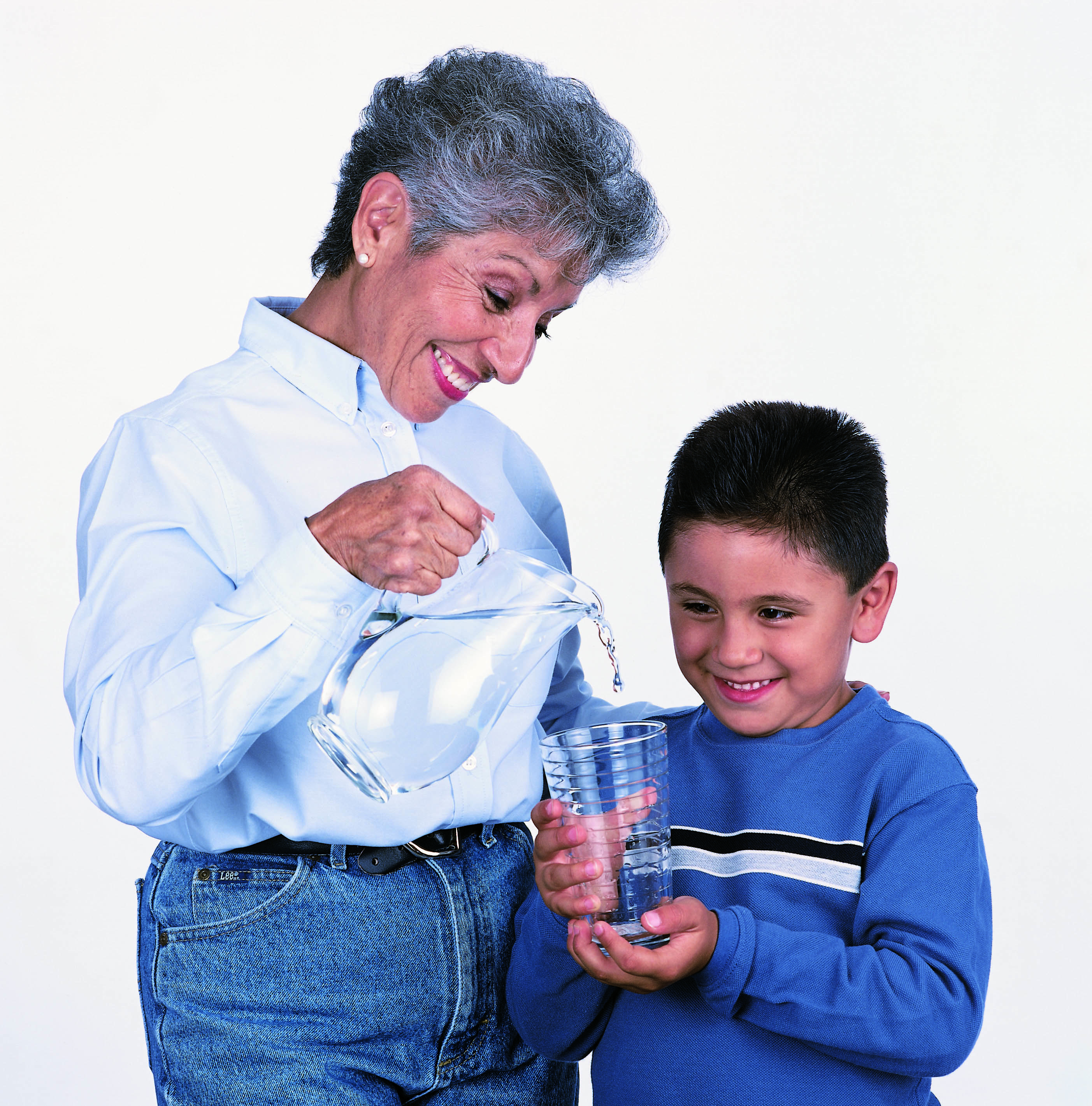 Woman filling a glass of clean water for her grandson