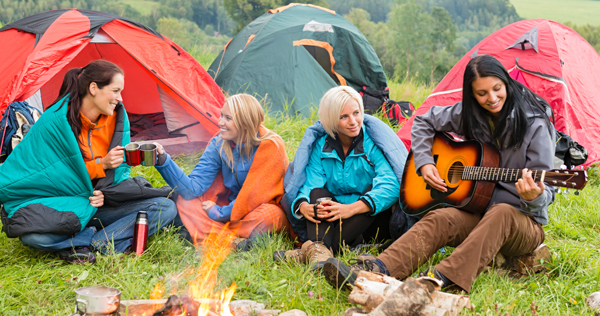 Four people around a campfire talking and listening to one of them playing guitar.
