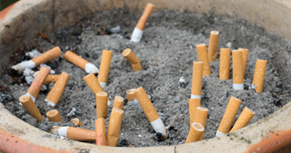 Close up picture of a clay pot filled with sand and several extinguished cigarette butts