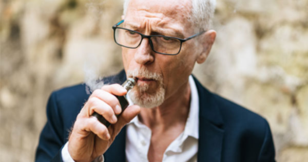 Photgraph of a mature man with gray hair and black glasses wearing a blue blazer jacket and white shirt and smoking an e-cigerette.  Smoke is puffing from it.