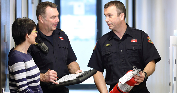 Close-up image of two Halifax Regional Fire & Emergency Station Officers conducting a Fire Safety Maintenance Inspection of a building while having a friendly conversation with a female property representative. One Officer is holding a portable fire extinguisher.