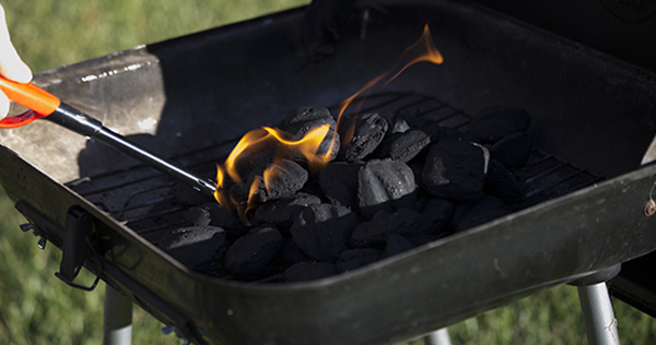 Close up image of a person using a propane barbecue lighter to light charcoal briquettes
