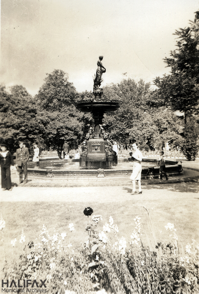 Black and white image of a fountain with a young woman, a small child, and two military servicemen nearby