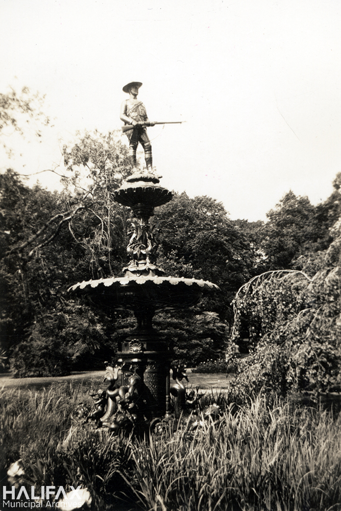 Black and white image of a fountain with a soldier holding a rifle on top, commemorating the Boer War