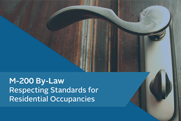 Close up image of a lever handle to a door on the right side of the image and a text box with a blue background and the words M-200 By-Law Respecting Standards for Residential Occupancies on the lower left side