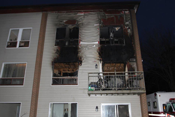Image of a three storey building with blackened and melted vinyl on the upper two units from a recent structure fire.