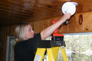 Close up image of a blond woman on a yellow step ladder changing the batteries in the smoke alarm on the ceiling