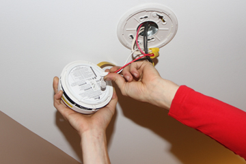 Close up image of a certified electrician's hands working at the ceiling plugging in the pig tail section of a wired smoke alarm