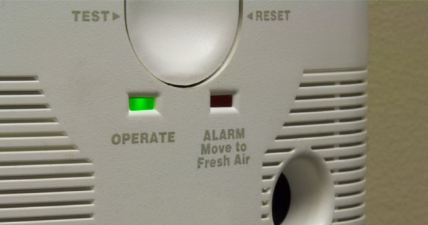 Close up image of a Carbon Monoxide alarm showing a green operating light and a test and reset button.