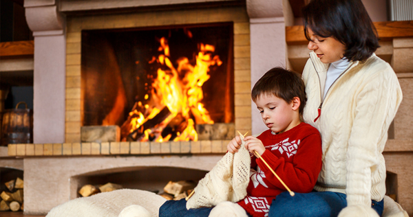 Image of a mother and young son sitting on a large cusion in front of a fire in a fireplace while the Mom is teaching her son to knit.