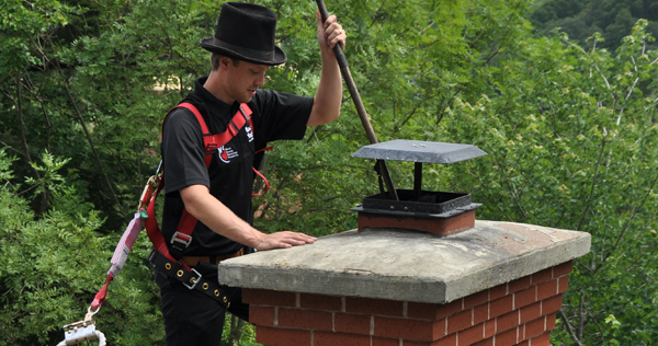 Close up image of a man wearing an old style chimney sweep top hat and a modern safety harness up on the roof on a building cleaning a chimney flue