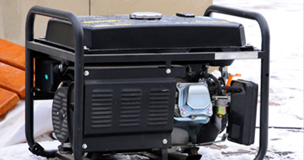 Image of a generator outside on the snow covered ground.