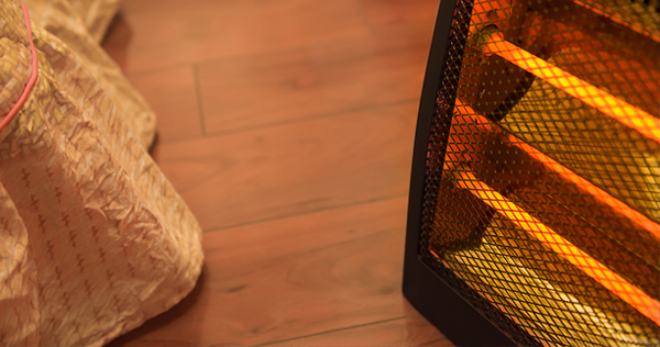 Close up image of a portable space heater turned on high and located only 10 inches or so from a bed with a bedskirt.