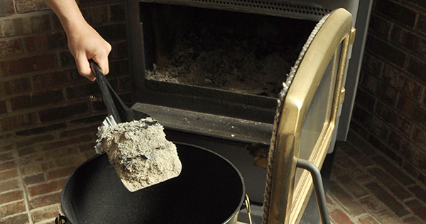 Close up image showing a woodstove with the door open and a persons hand holding a small metal shovel is removing the ashes from the woodstove and placing them in a black metal ash bucket.