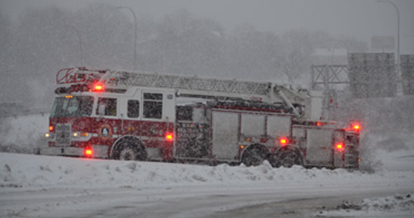 Image of a Fire Truck stopped on the side of the road with lights flashing during a winter storm.