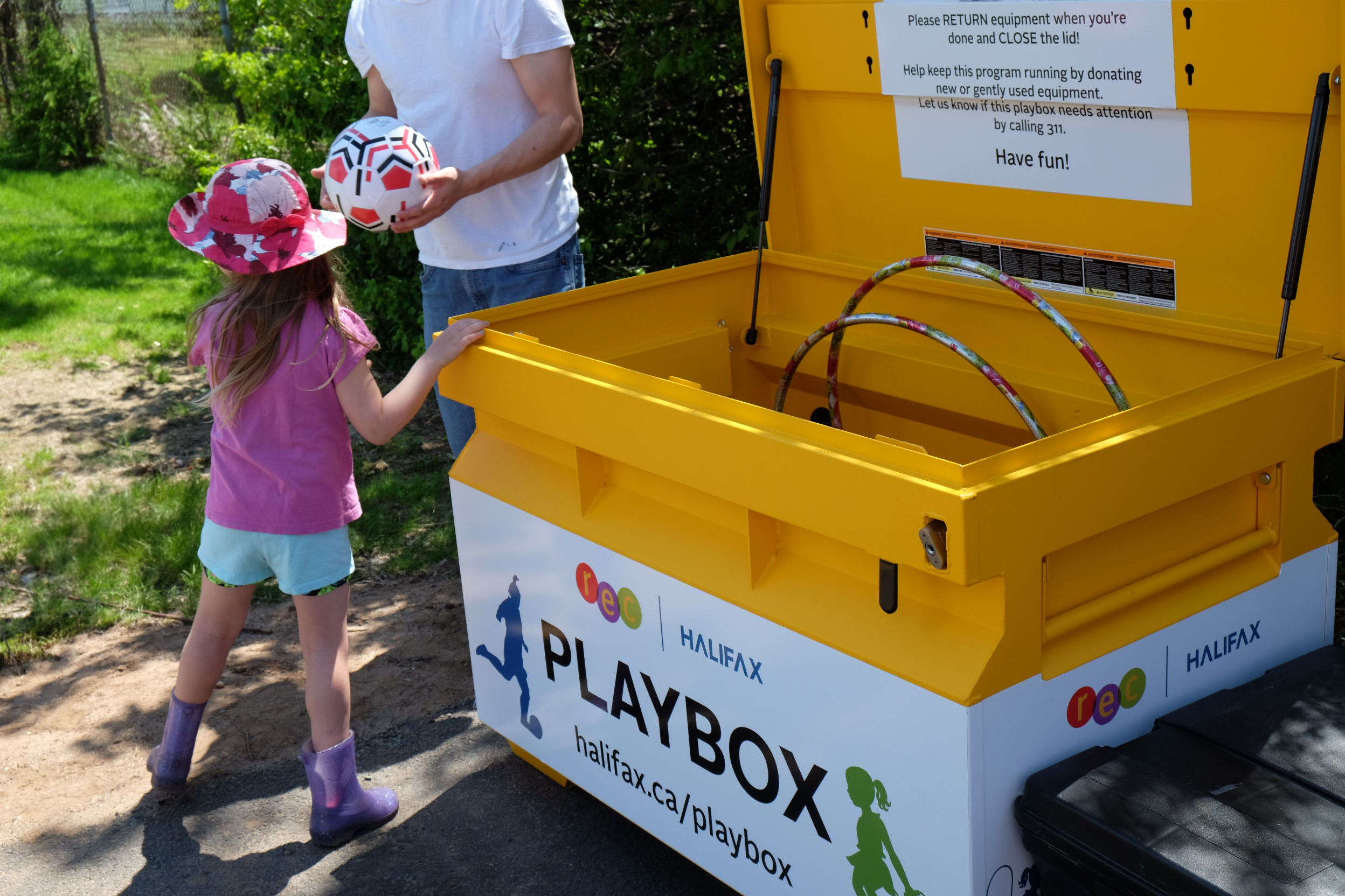 A child and parent borrowing a soccer ball from the playbox