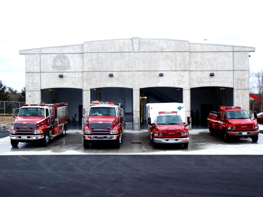 A photo of fire fighting vehicles outside of a fire station